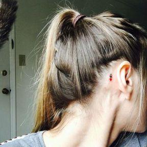 Tatouage discret lettre derrière l'oreille